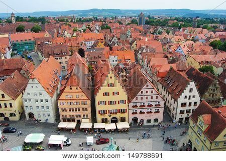 Rothenburg ob der Tauber, Germany - July 26, 2014. View over Rothenburg ob der Tauber, with historic buildings, people, cars and market stalls.