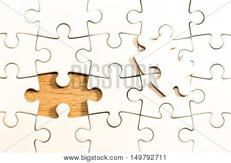 white jigsaw/puzzle whit one gap over a wooden table background symbol of problem solving