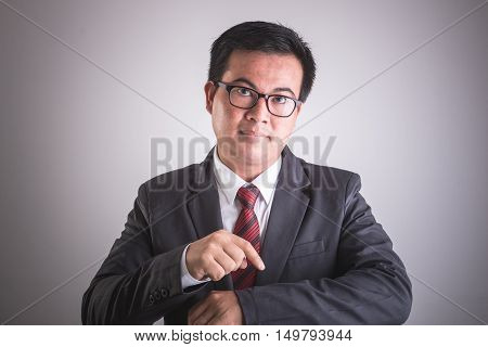 Portrait Of Asian Businessman With Hand Point On His Wrist. Time Checking Or Punctually Concept. Stu