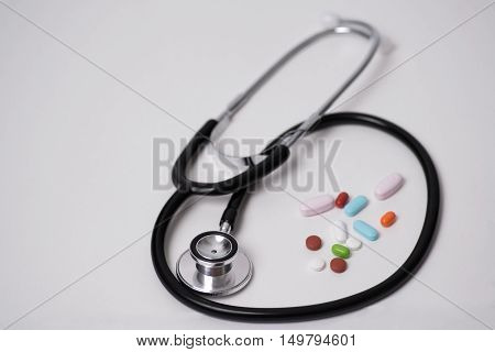 Stethoscope and pills, Dr. appointment, or an office visit, for a patient.
