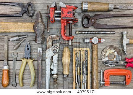 Old Hand Tools Set Including Clamps, Hammer, Screwdriver, Wrenches And Pliers On Grey Wooden Boards
