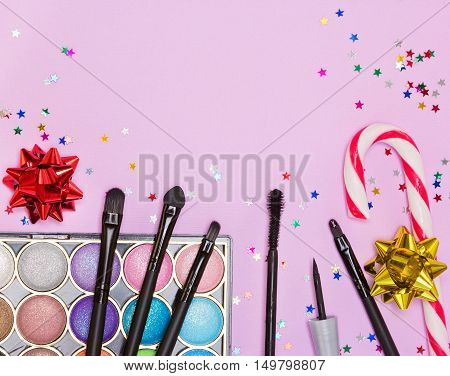 Christmas party makeup. Bright color glitter eyeshadow, mascara, eyeliner, red lip gloss, make up brushes and applicator with candy cane, gift wrap bows and confetti on pink background. Copy space