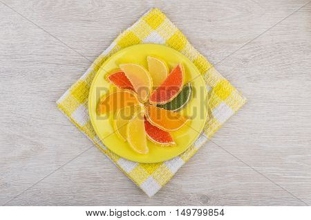 Marmalade In Form Of Citrus Fruits In Saucer On Napkin