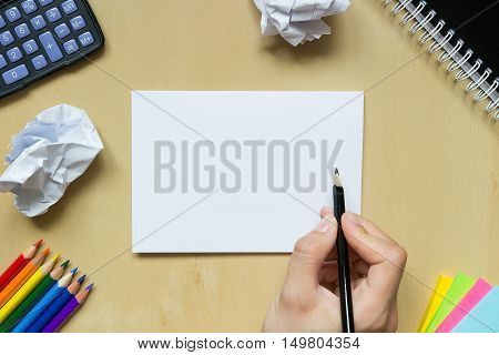 Scrap Of Crumpled Paper And Hand With A Pen On A Desk