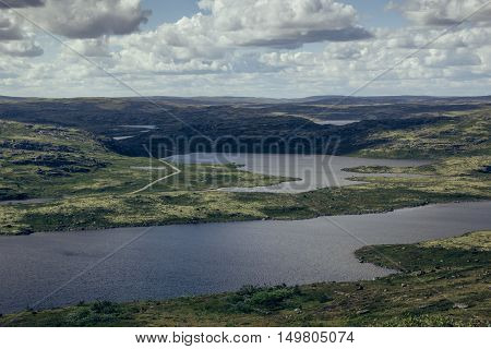 Highlands valley with views of the lakes and the green hills in sunny cloudy day. Arctic summer the tundra Norway.
