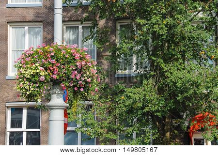 Decorative flowers on a pole near the building in Amsterdam the Netherlands