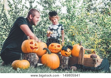 Daughter Near Father Who Pulls Seeds And Fibrous Material From A Pumpkin Before Carving For Hallowee
