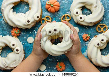 Happy and scary Halloween - treat for kids in the form of ghost choux pastry cake with chocolate in children's hands top view
