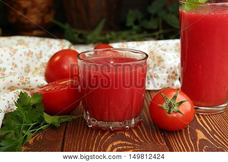 Two glasses of tomato juice and fresh tomatoes on wooden table
