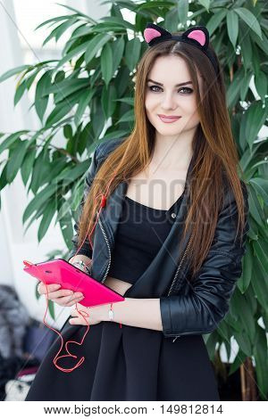 Stylish girl model wearing cat ears holding pink tablet and listen music. Indoor young female portrait wearing leather jacket and black skirt. Fashion lady with long brown hair wear cool outfit