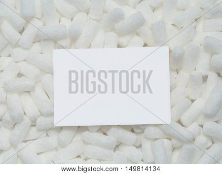 Blank sheet of white paper card with copy space for your text lying on the styrofoam packing peanuts. Packaging filling polystyrene bits top view, closeup.