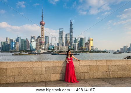 Shanghai China - October 26 2013: Chinese woman in a long red dress at the Bund. It is a waterfront area central Shanghai which runs along the western bank of Huangpu River facing Pudong skyscrapers Shanghai China