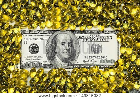 Yellow macro drug pills, fish oil capsules on one hundred dollars banknote as a background. Money and health still life concept.