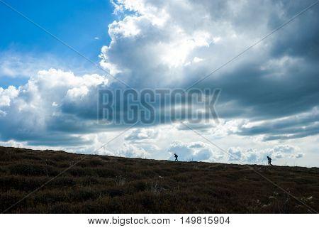 Man climbs up the hill. Mountain climbing. Hiking. Impressive skies.