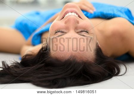 Cute Young Woman Grinning As She Relaxes In Bed