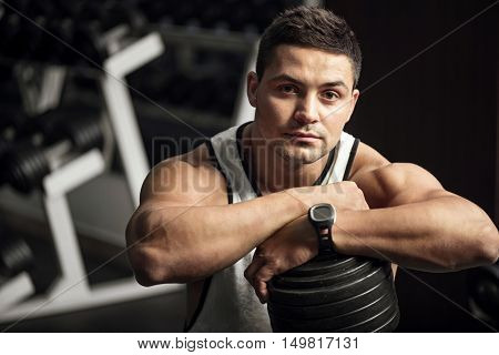 Intensive training. Serious determined well built man standing in a gym and leaning on a dumbbell while looking at you