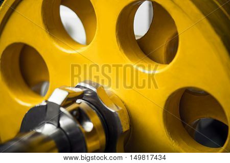 Equipment for weightlifting training. Close up of a yellow metallic heavy barbell in a gym