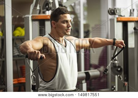 Strong and athletic. Young handsome serious sportsman sitting on a gym apparatus and holding his hands up while working out