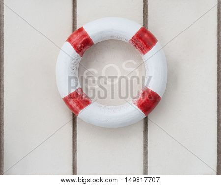 Wooden life buoy on wood with the letters SOS