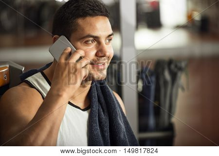 Interesting conversation. Good looking athletic professional sportsman talking on the phone and smiling while taking pleasure in the conversation
