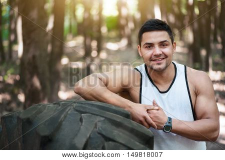 Great mood. Strong athletic cheerful man leaning on the large tire and smiling while being in the park