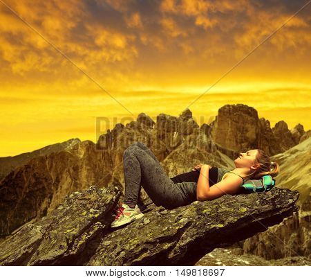 Tourist lying on a rock in Dolomites at sunset, Italien Alps.