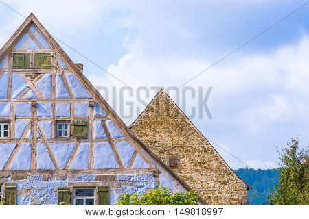 Antique German gable roofs and facades against sky - Architectural details from two medieval German houses one with blue half timbered walls small windows wooden shutters and one with aged stone wall and a single wooden window.