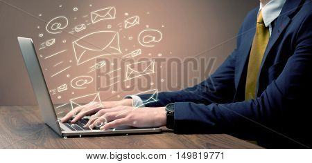 An office worker sending emails and communication with clients with the help of a portable laptop on desk concept