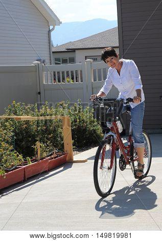 Mature female beauty riding her bike outside.