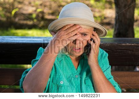Scared woman with cell phone. Senior lady in a hat. Children are in trouble. No time to think.