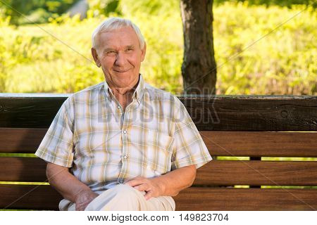 Smiling elderly man. Senior male on bench. Memories of good old times. I achieved everything I wanted.