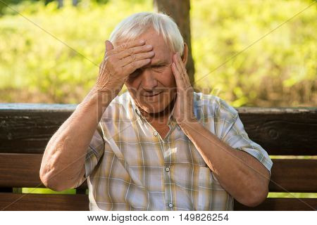 Senior man holding his head. Elderly guy has headache. Blood pressure has increased. Problem with health.