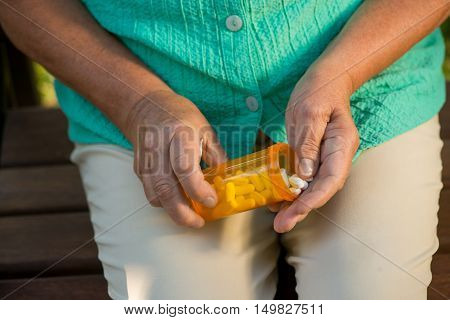 Hand of woman holding pills. Orange tablet bottle. New strong antibiotic. Protect your health.