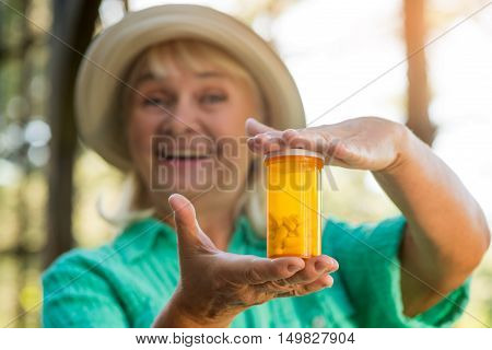 Smiling woman with pill bottle. Lady holding medicine container. New type of antidepressant. Use the smallest dose.