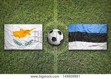 Cyprus vs. Estonia flags on green soccer field, 3D illustration