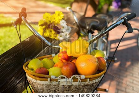 Basket filled with fruits. Bicycle near fence. Vitamins and energy of sun. Juicy apples and sweet peaches.