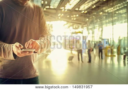 Man using smart phone at Check in Counter and Passengers in a airport departure terminal.