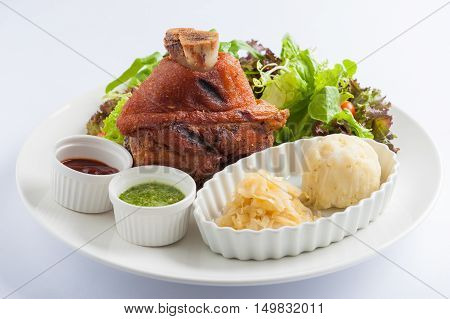 German Pork Hocks or pork knuckle with barbecue sauce Thai spicy sauce mashed potatoes pickled cauliflower and fresh vegetables in ceramic dish