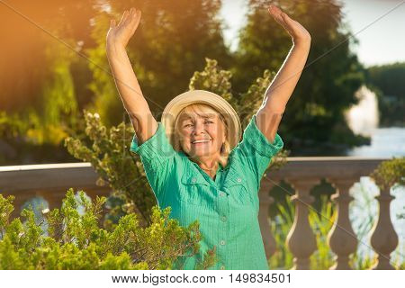 Senior woman with raised arms. Smiling lady on nature background. Health starts from good mood. Best trip ever.