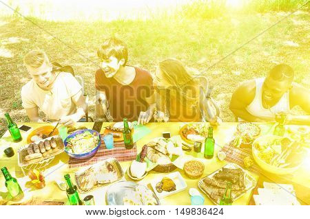 Group of multiracial friends having barbecue on summer day - Young cheerful students cheering and toasting beer in backyard - Warm filter with sun halo flare
