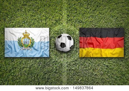 San Marino vs. Germany flags on green soccer field, 3D illustration