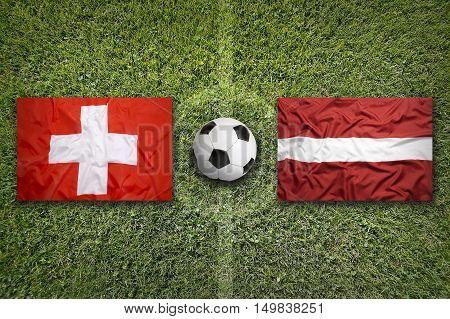 Switzerland vs. Latvia flags on green soccer field, 3D illustration