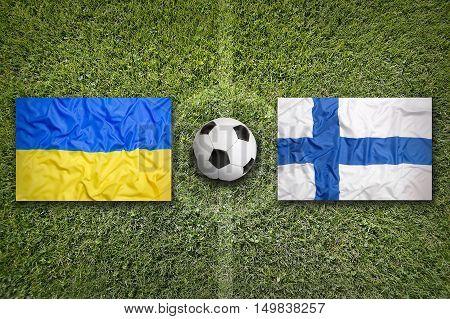 Ukraine vs. Finland flags on green soccer field, 3D illustration