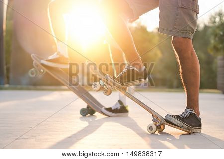 Closeup of two friends training with skateboard at sunset outdoors - Skaters standing on their longboards with back lighting - Extreme sport concept - Soft warm filter