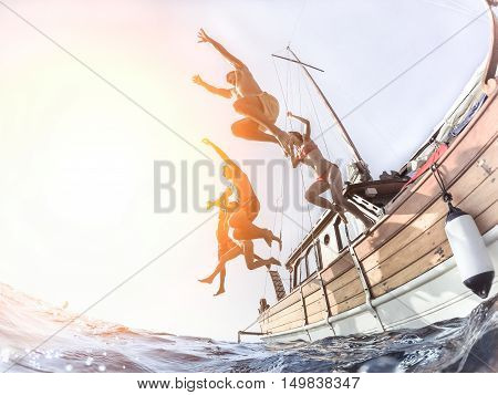 Multiracial young people diving from sailing boat into the sea - Cheerful friends having fun in summer party day - Vacation and friendship concept - Fisheye lens distortion