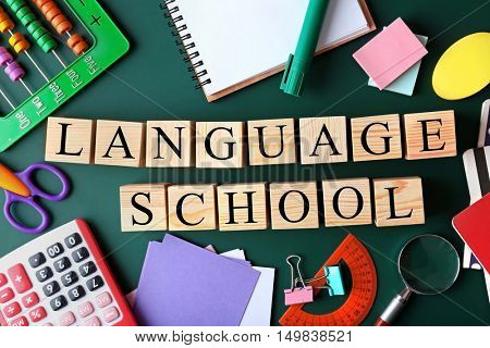 Colourful stationery and words LANGUAGE SCHOOL on chalkboard