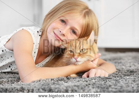 Beautiful little girl lying on floor with red fluffy cat