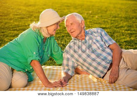 Senior people on meadow. Couple looking at each other. I'm always with you. Warmth of our hearts.