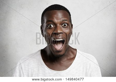 Omg! Portrait Of Astonished Wide-eyed African Customer In White T-shirt Looking At Camera In Surpris