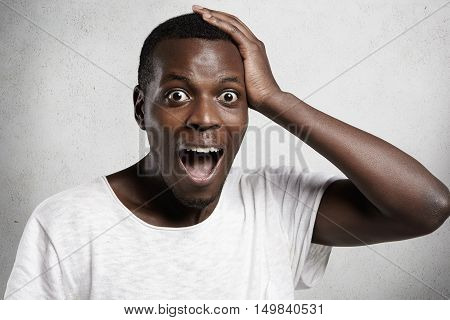 Shocked Or Surprised Young Handsome African Man Shouting In Horror Or Fear With Hand On Head And Mou